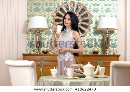 Beautiful brunette in long evening dress offers a taste of the cake and cup of tea .  She holds a cup of tea in his hands. - stock photo