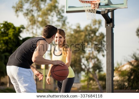 Beautiful brunette in sporty outfit trying to steal the ball during a basketball game against her boyfriend - stock photo