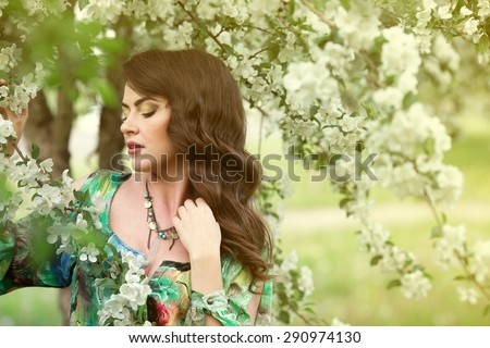 beautiful brunette in the garden of blooming apple trees - stock photo
