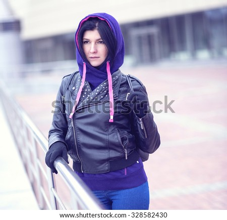 Beautiful brunette in the hood in the autumn, on the street. Fashion lifestyle. Close-up on a cloudy day, a young girl in the street, fashion hipster, outdoors in the spring. - stock photo