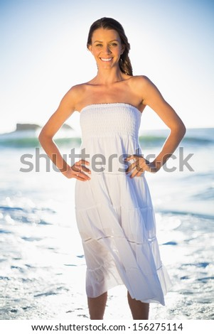 Beautiful brunette in white summer dress posing on the beach at dusk