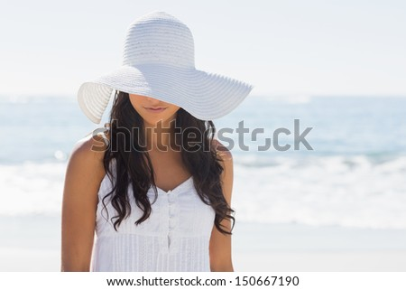 Beautiful brunette in white sunhat looking down at the beach - stock photo