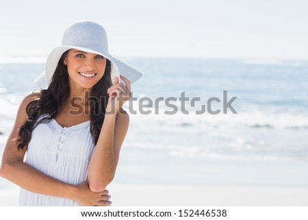 Beautiful brunette in white sunhat smiling at camera on the beach - stock photo