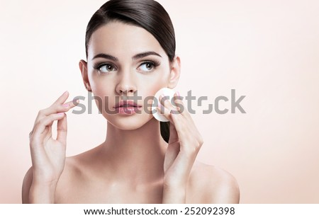 Beautiful brunette lady removing makeup from her face, skin care concept / photoset of attractive brunette girl on beige background  - stock photo
