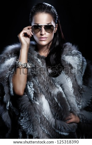Beautiful brunette lady wearing fur and sunglasses. Fashionable photo. - stock photo