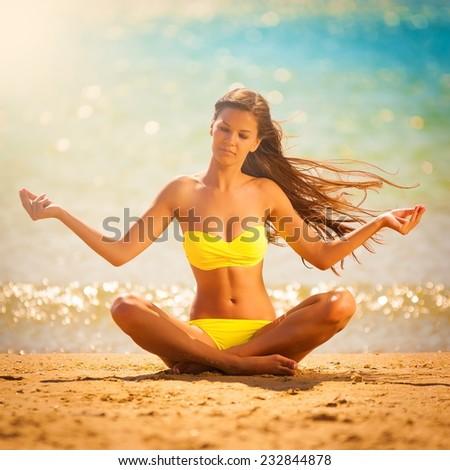 beautiful  brunette lady woman in yellow bikini posing  meditation yoga in tropical  blue sea water bali has sports and tan body - stock photo