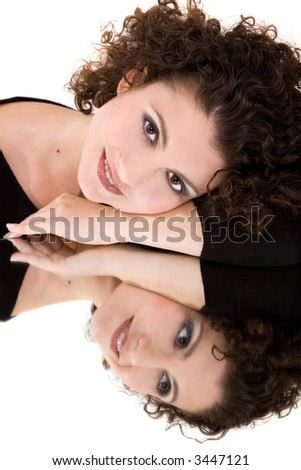 Beautiful brunette leaning on a mirror with her reflection - stock photo