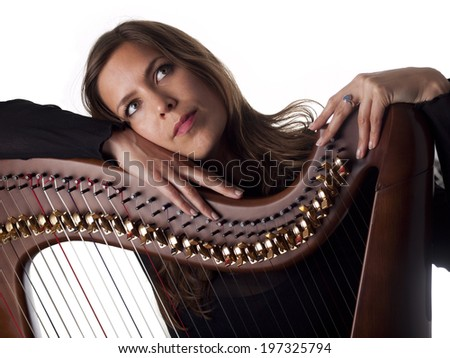 beautiful brunette leaning on her classical harp isolated over a white background - stock photo