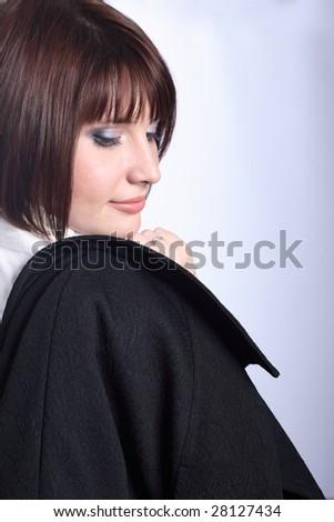 Beautiful brunette looking over right shoulder. Coat in hand - stock photo