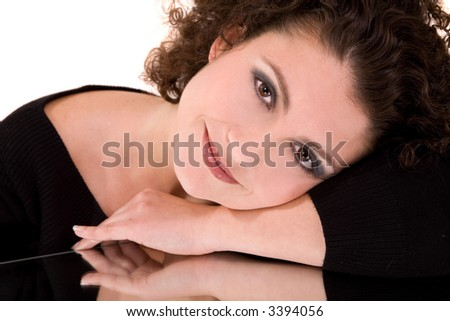 Beautiful brunette lying on a mirror with a relaxed smile - stock photo