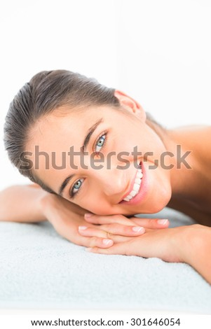 Beautiful brunette lying on massage table smiling at camera at the health spa - stock photo