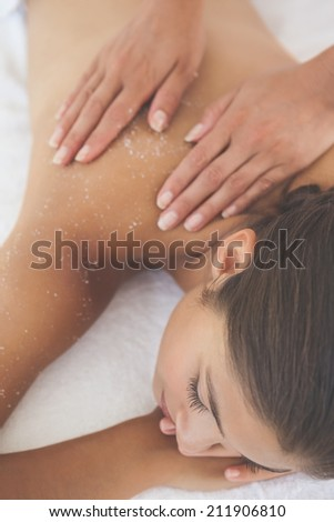 Beautiful brunette lying on massage table with salt scrub on back at the health spa - stock photo