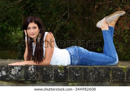 Beautiful brunette lying on the small wooden bridge. - stock photo