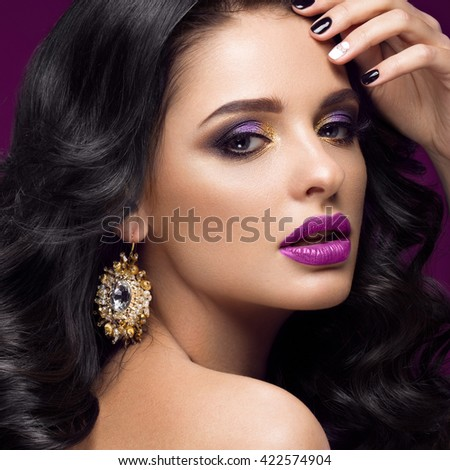 Beautiful brunette model: curls, classic makeup, gold jewelry and purple lips. The beauty face.