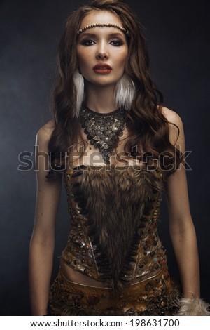 Beautiful brunette model dressed as Indian posing in studio - stock photo