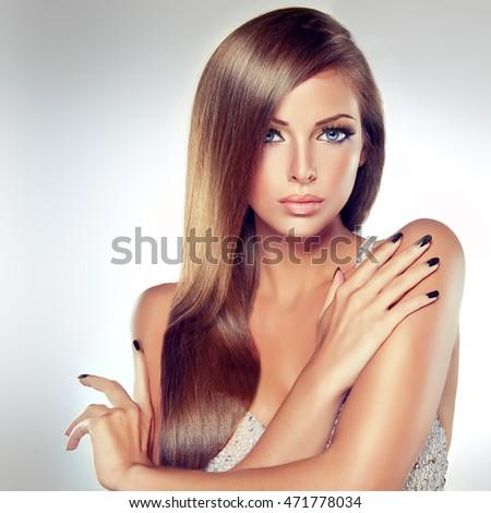 Đẹp mô hình brunette cô gái với mái tóc dài thẳng mượt.  Một phụ nữ trong một chiếc váy màu bạc và làm móng tay bạc trên móng tay