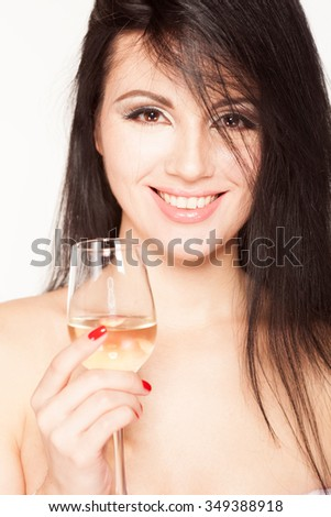 Beautiful brunette model in a Christmas suit with a glass of champagne - stock photo