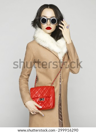Beautiful brunette model in fashion clothes posing in studio. Wearing coat, handbag, sunglasses - stock photo