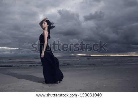 Beautiful brunette model in long black dress standing on the beach. Cloudy weather. Sunset - stock photo