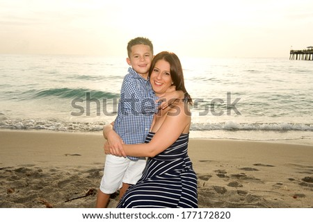 Beautiful brunette mother and son hugging at the beach at sunrise  - stock photo