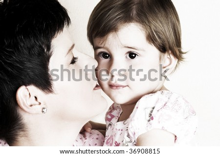 Beautiful brunette mother holding her cute daughter - stock photo