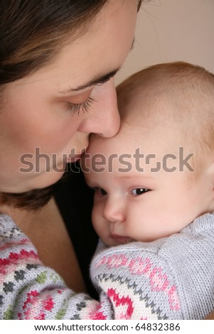 Beautiful brunette mother holding her two month old baby girl