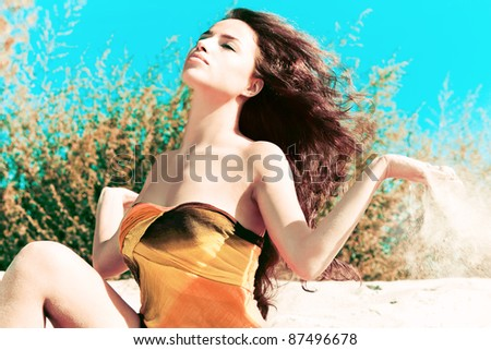 beautiful brunette on the beach with sand in hands, wind in hair, summer day
