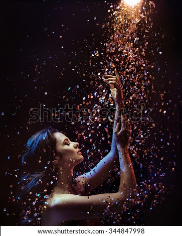 Beautiful brunette over sparkly particles background - stock photo