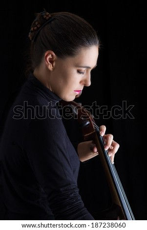 Beautiful brunette playing a cello with selective light in black dress - stock photo