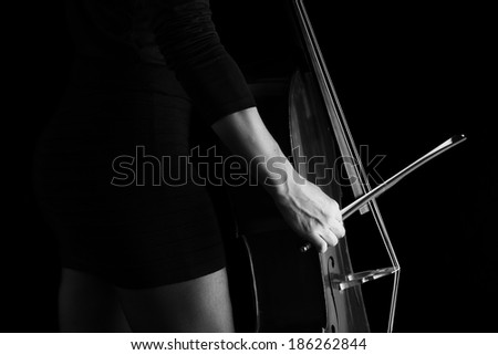 Beautiful brunette playing a cello with selective light in black dress artistic conversion - stock photo