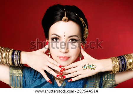 Beautiful brunette portrait with traditional costume. Indian style-red background - stock photo