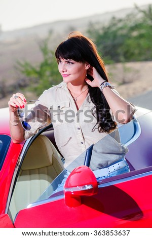 Beautiful brunette poses in front of the car in the yellow desert.