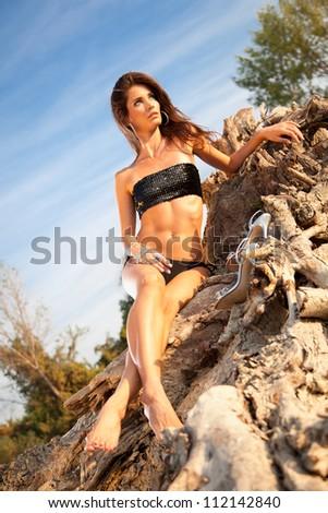 Beautiful brunette posing  on river bank.. Art photo. - stock photo