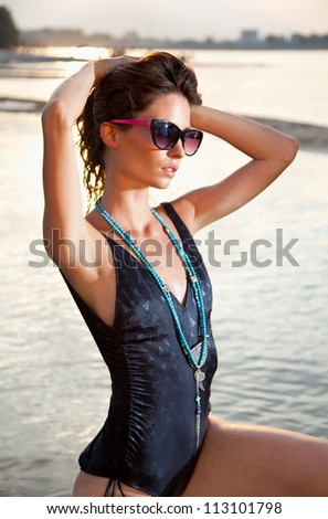 Beautiful brunette posing  on river bank.  Art photo. - stock photo