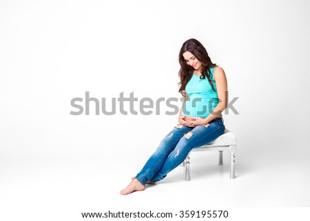 beautiful brunette pregnant woman. attractive mom in the blue t-shirt and jeans - stock photo