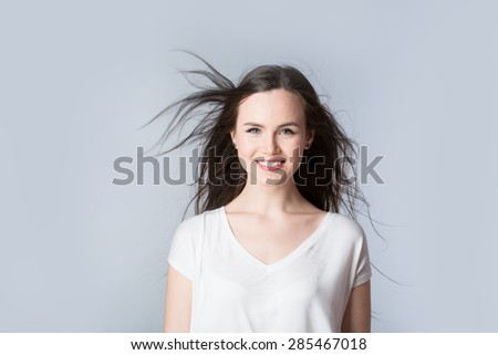 Beautiful brunette. Purposeful woman with hair in the wind. - stock photo