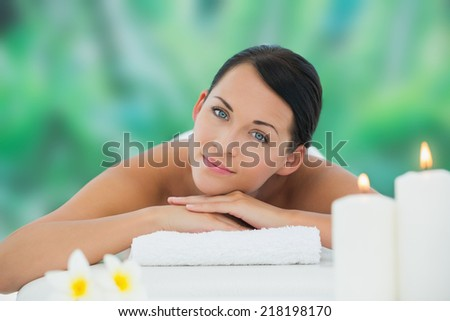Beautiful brunette relaxing on massage table smiling at camera at a luxury spa - stock photo