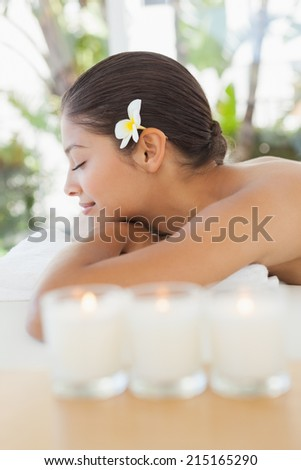 Beautiful brunette relaxing on massage table with salt scrub on back at the health spa - stock photo