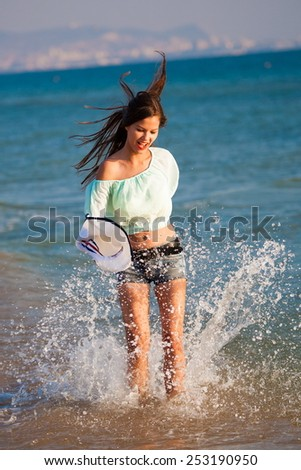 beautiful  brunette  sexy  smiling  woman in blue jeans shorts, blouse and white hat in sea water background have  tan skin, red lips  and sport  body - stock photo