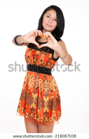 Beautiful brunette shows a heart symbol on white background