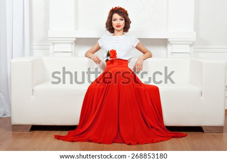 Beautiful brunette sitting in the middle of a white sofa in her hand a red flower. - stock photo