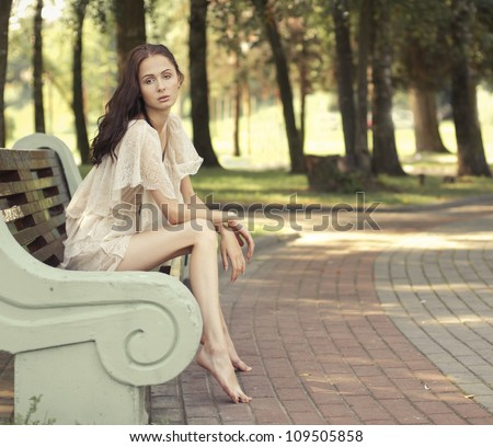 beautiful brunette sitting on a bench in the waiting - stock photo