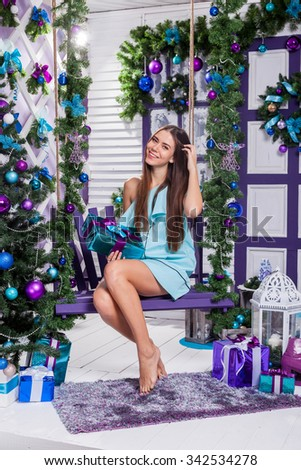 beautiful brunette sitting on a swing in a turquoise dress among Christmas toys and gifts near the Christmas tree decorated with Christmas balls. - stock photo