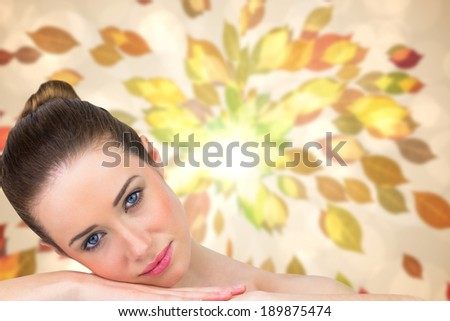 Beautiful brunette smiling at camera against autumnal leaf pattern in warm tones - stock photo