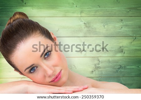 Beautiful brunette smiling at camera against wooden planks - stock photo