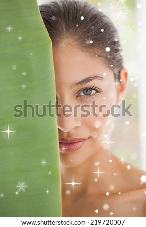 Beautiful brunette smiling at camera behind leaf against snow falling