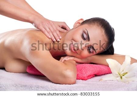 Beautiful brunette spa woman getting massage on towel in spa salon - stock photo