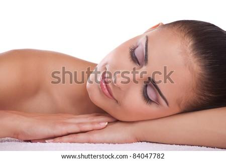 Beautiful brunette spa woman lying on towel in spa salon - stock photo