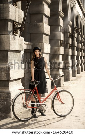 Beautiful brunette standing near her old bicycle over city background. Retro style.