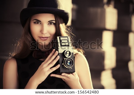 Beautiful brunette standing on a city street and holding the old camera. Retro style.